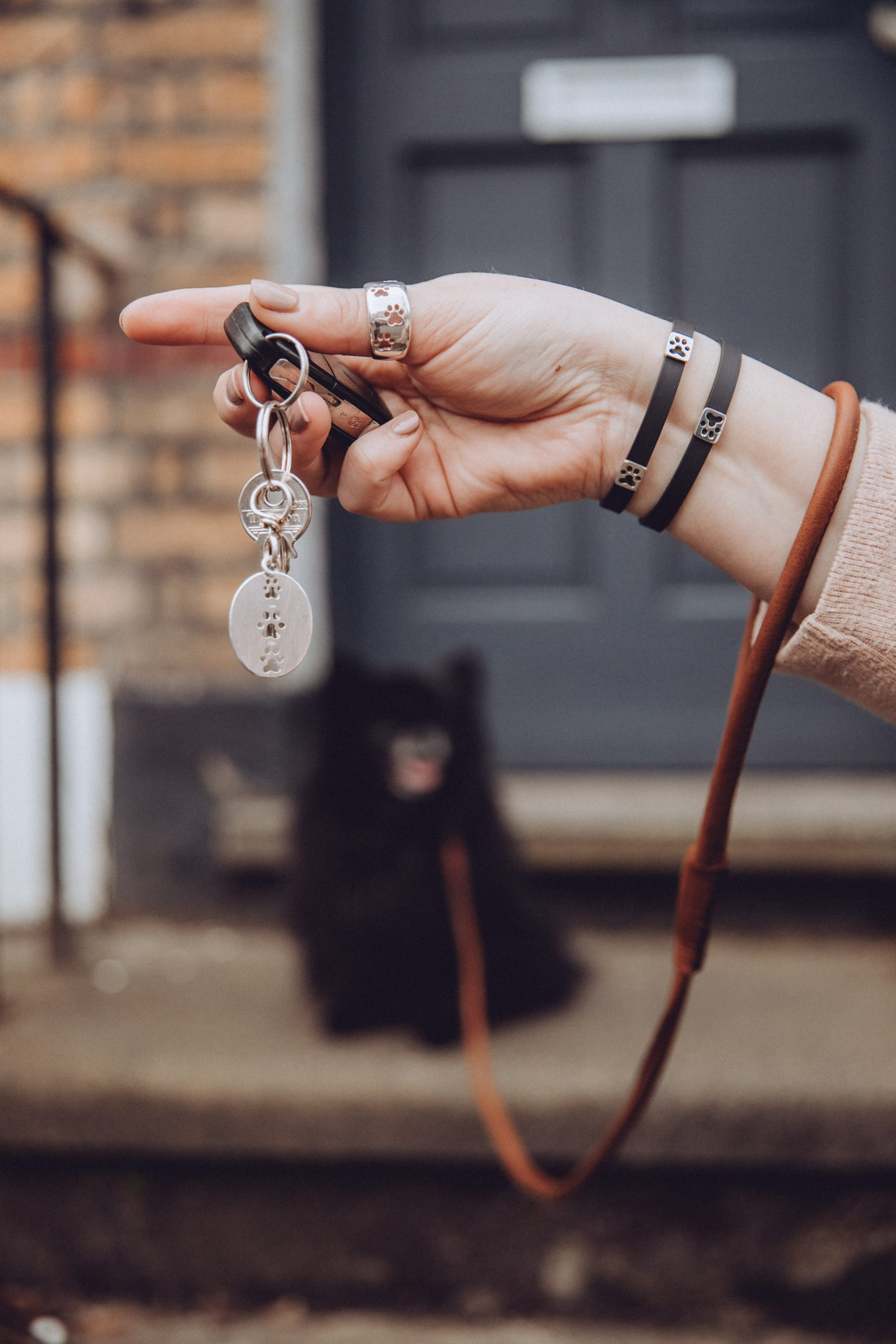 Silver key ring attached to car keys, while Kimberly wears the silver paw print ring, and rubber paw print bracelets