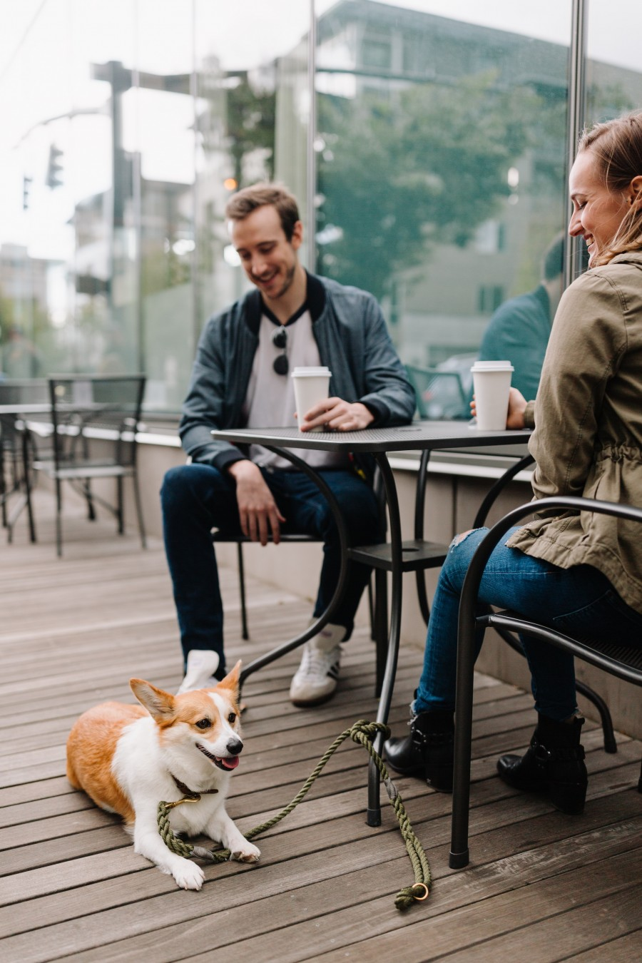 dog relaxing at owners feet at an outside coffee shop